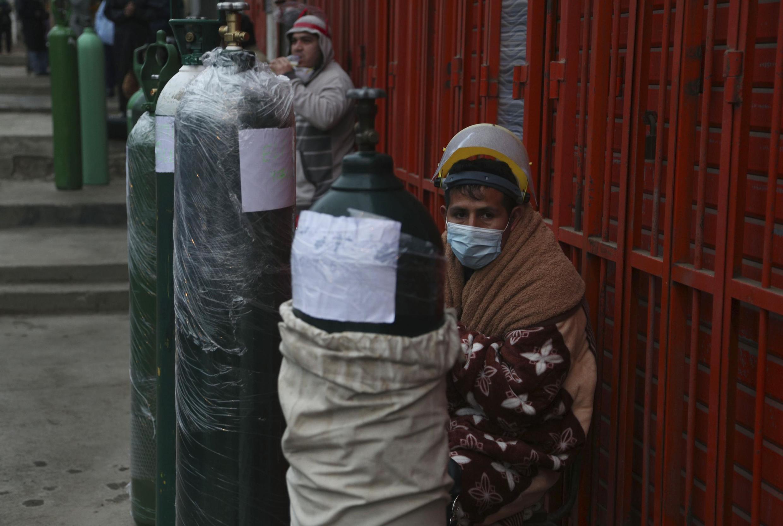 Les gens font la queue avec leurs bouteilles d'oxygène vides pour les remplir dans un magasin du quartier de San Juan à Lima, le lundi 3 août 2020, pour porter secours à des proches atteints par le coronavirus.