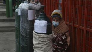 Des gens font la queue avec leurs bouteilles d'oxygène vides pour les remplir dans un magasin du quartier de San Juan à Lima, le lundi 3 août, afin de porter secours à des proches atteints par le coronavirus.
