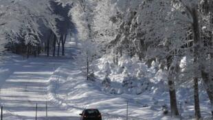 Um carro transita em uma estrada coberta de neve nos arredores de Estrasburgo, na França