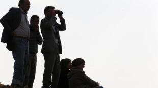 Turcos curdos na cidade de Suruc, da província turca de Sanliurfa, observam os bombardios em Kobane, na Síria.