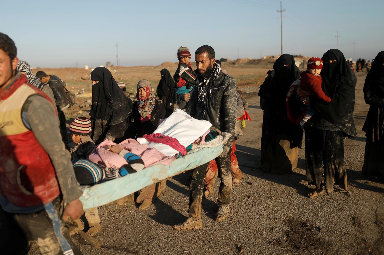 Desplazados iraquíes huyen de sus casas llevando a un niño herido (Mahmud, 9 años) en uno de los ataques entre las fuerzas armadas iraquíes y los yihadistas del EI en la parte oeste de Mosul.