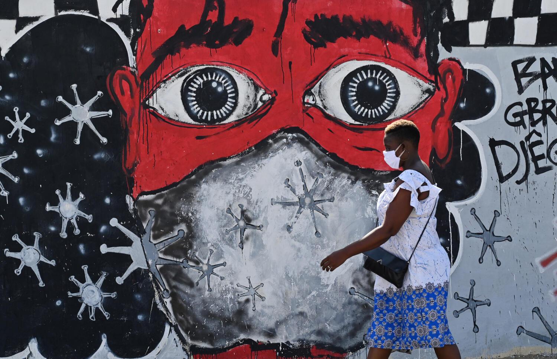 Une femme passant devant une fresque décrivant les mesures d'hygiène à adopter avec le coronavirus à Abidjan, le 15 mai 2020. (Photo d'illustration)