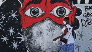 Une femme passant devant une fresque décrivant les mesures d'hygiène à adopter avec le coronavirus à Abidjan, le 15 mai 2020.