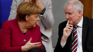 This file photo shows German Chancellor Angela Merkel talking to Interior Minister Horst Seehofer during a session of the Bundestag in Berlin.
