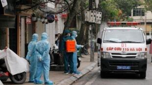 Nhân viên y tế đang khử trùng một chiếc xe cứu thương gần nhà một người bị nhiễm virus corona trên một con phố bị cách ly ở Hà Nội. Ảnh chụp ngày 07/03/2020.