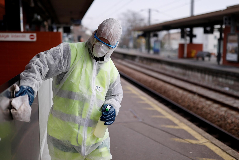 Un travailleur nettoie la gare avec un désinfectant pour ralentir la propagation du coronavirus à Suresnes.