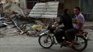 Sírios passam em frente a prédios destruídos pela guerra civil em Aleppo, nesta segunda-feira.