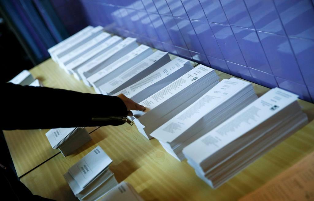 Eleitor pega uma das cédulas para votar.