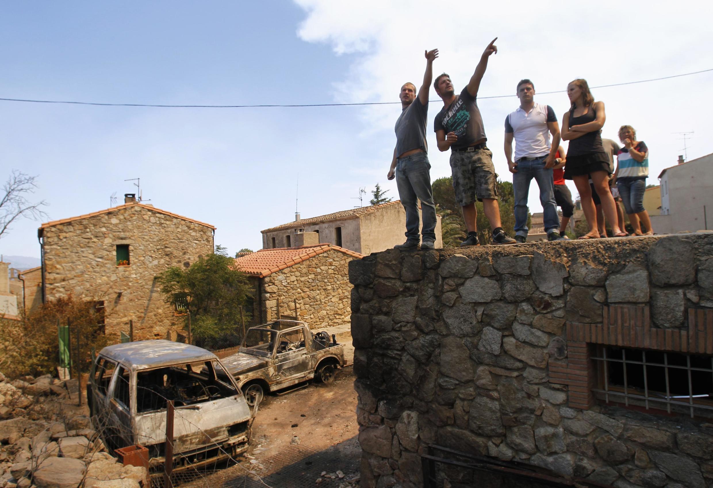 Village d'Agullana, Catalogne, le 23 juillet 2012. Derrière, deux voitures portent les stigmates de l'incendie.