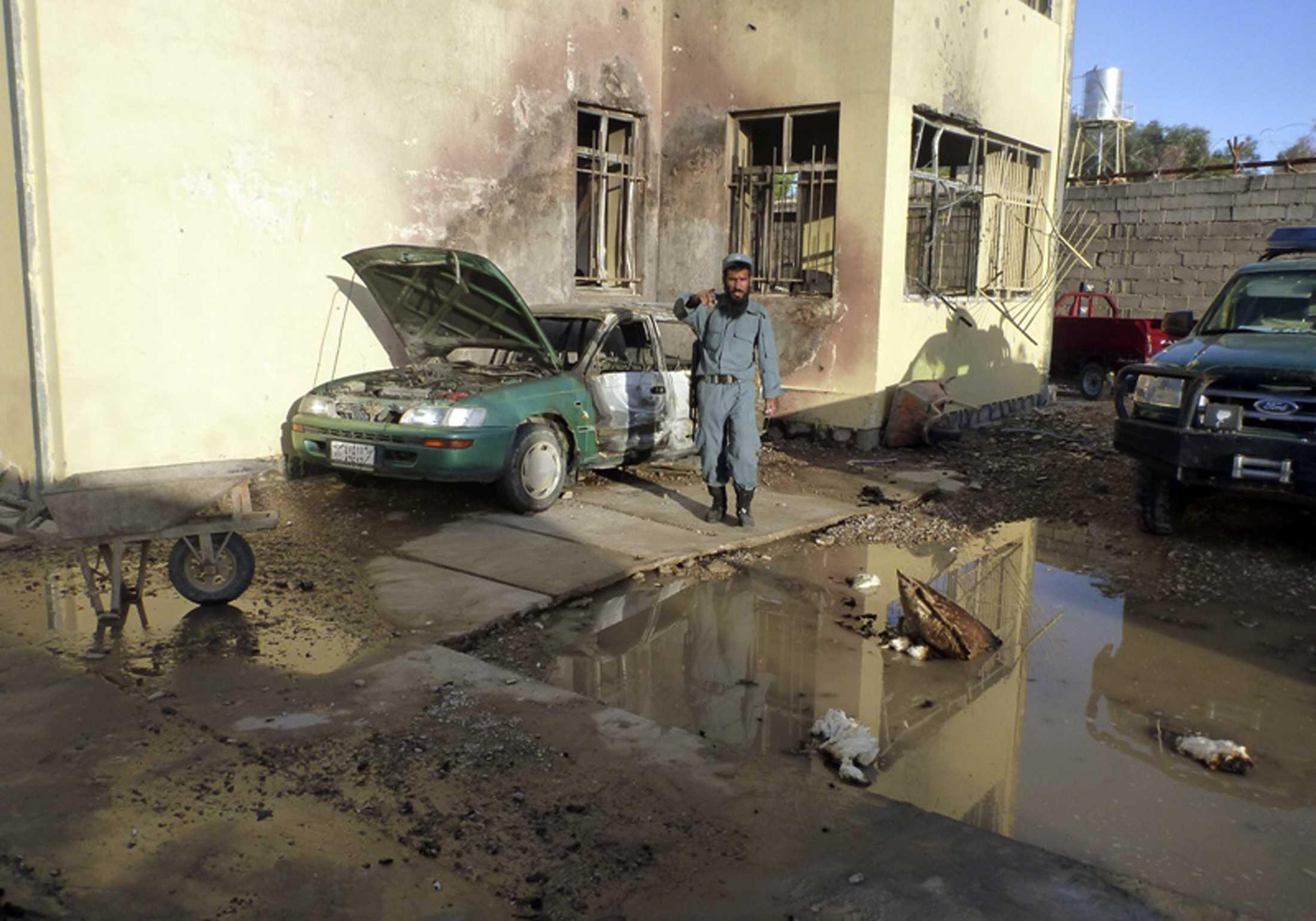 An Afghan policeman gestures at the site of a Taliban attack in Farah province this week