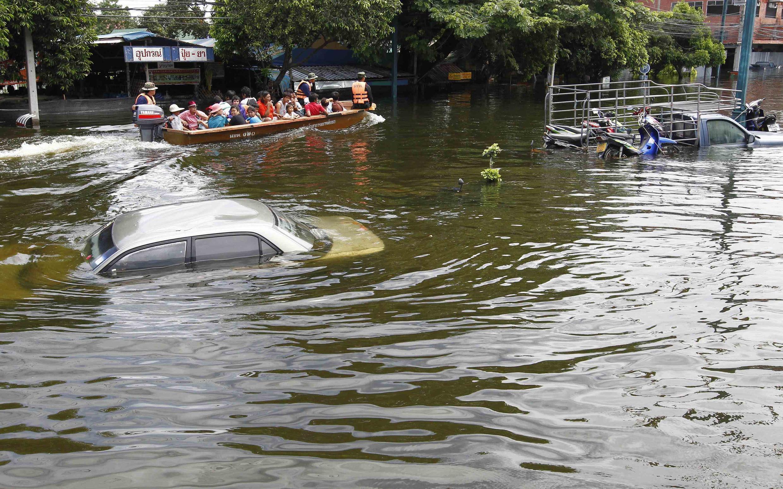 Des Thaïlandais empruntent une barque pour traverser une rue inondée de la province d'Ayutthaya, le 14 octobre 2011.