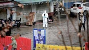 Trabalhadores com roupas protetoras perto do mercado de peixe de Wuhan, onde começou a epidemia