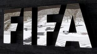 The snow-covered landscape is reflected in a logo in front of FIFA headquarters in Zurich, Switzerland, January 10, 2017.