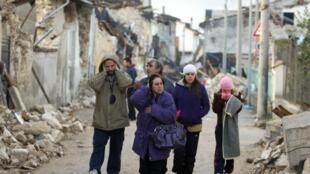 Una familia camina en las calles de L'Aquila tras el terremoto.
