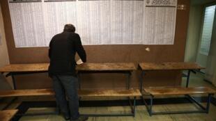 Législatives en Iran ce vendredi 21 février: dans un bureau de vote de Téhéran, un assesseur vérifie les listes des candidats.