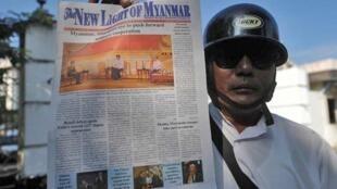 Un vendeur montre la nouvelle version du quotidien gouvernemental «The New Light of Myanmar», dont la première page est en couleur.