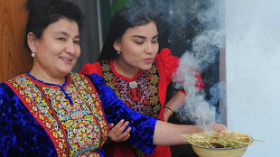 Turkmen women wearing traditional dress demonstrate how to fumigate a house with the smoke of burning wild rue