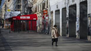 Uma mulher caminha pela avenida Champs Elysees quase vazia em Paris, sábado, 31 de outubro de 2020.