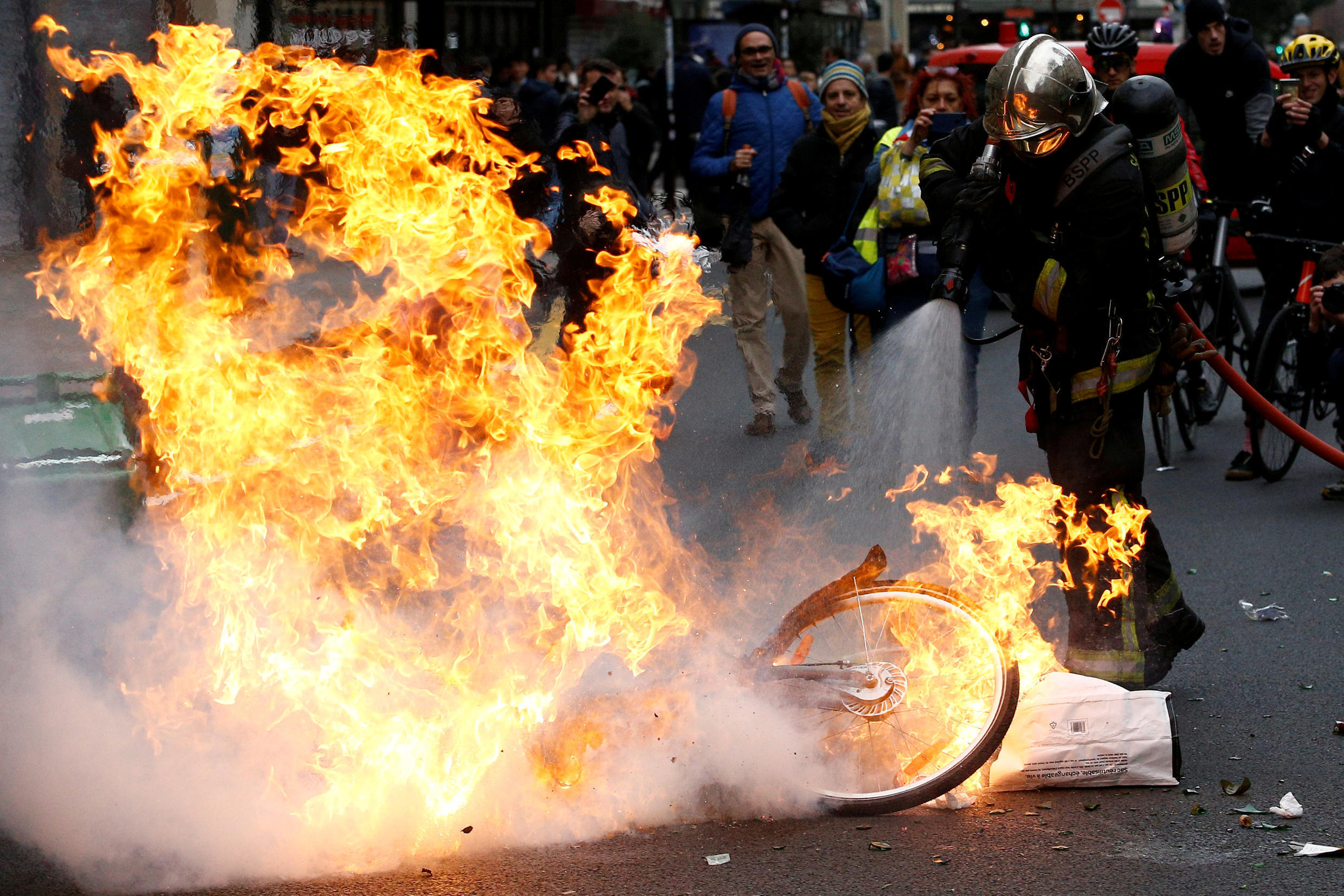 "A fireman extinguishes a burning bicycle during clashes with yellow vests protesters as part of a national day of protest by the ""yellow vests"" movement in Paris, France, December 8, 2018."