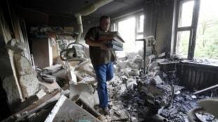 Um homem retira livros e documentos de local bombardeado em Donetsk.