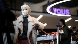 Travellers wearing masks arrive on a direct flight from China to Paris