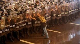 Un manifestant thaïlandais face à la police lors d'une manifestation, à Bangkok, le 16 octobre 2020.