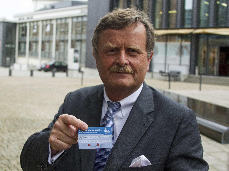 Le président de l'ordre des médecins allemands, Frank Montgomery, montrant sa carte de donneur d'organes, à Berlin, le 9 août 2012.