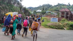 Des réfugiés de la République Démocratique du Congo portent leurs effets personnels en passant près des bureaux du HCR au camp de réfugiés de Kiziba, au Rwanda, le 21 février 2018.