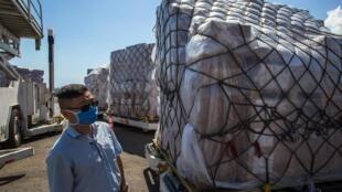 Um membro da Embaixada da China verifica a chegada de um carregamento de 55 toneladas de ajuda humanitária e equipamento médico enviado da China para a luta contra a propagação do coronavírus, COVID-19, no Aeroporto Internacional Simon Bolívar em Maiquetia, Estado de Vargas, Venezuela, em 28 de Março de 2020.