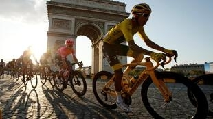 Эган Берналь (в желтом) на фоне Триумфальной арки. Финальный этап Тур де Франс-2019, 28 июля 2019 года