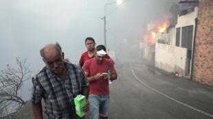 Moradores fogem do ar irrespirável nas ruas da localidade de Bom Sucesso, próximo de Funchal, na ilha da Madeira.