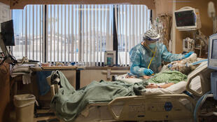 A nurse at the bedside of a coronavirus patient in an intensive care unit at Providence St. Mary's Medical Center in Apple Valley, California on January 11, 2021
