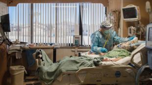 Uma enfermeira no leito de um paciente com coronavírus em uma unidade de terapia intensiva no Providence St. Mary's Medical Center em Apple Valley, Califórnia, em 11 de janeiro de 2021.