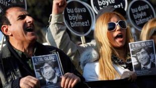 Des proches du journaliste Turco-Arménien assassiné Hrant Dink brandissent des photos et des panneaux sur lesquels on peut lire« cette affaire ne finira pas cette manière». Manifestation à côté du tribunal d'Istanbul, le 17 janvier 2012.