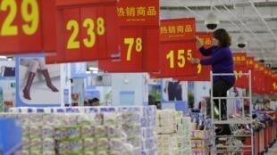 Một nhân viên thay đổi bảng giá tại một siêu thị ở Vũ Hán, Hồ Bắc, ngày 09/11/2012. Lạm phát làm thu nhập thực tế của người dân Trung Quốc giảm đi.