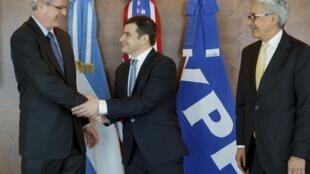 Miguel Galuccio (centro), presidente de empresa argentina YPF, y John S. Watson (izquierda), gerente de la compañía estadounidense Chevron, después de firmar un acuerdo en Buenos Aires el 16 de julio de 2013.