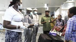 Funcionários do aeroporto internacional da Nigéria medem a temperatura dos passageiros que chegam da Guiné, da Libéria e de Serra Leoa.