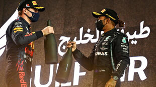 El piloto holandés de Red Bull, Max Verstappen (izq.), saluda al piloto británico de Mercedes, Lewis Hamilton, en el podio después del Gran Premio de Fórmula Uno de Bahréin, en el Circuito Internacional de Bahréin, en la ciudad de Sakhir, el 28 de marzo de 2021.