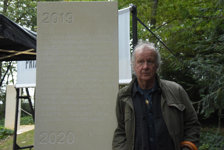Ed Vulliamy, jamais sans sa canne, s'adosse à la stèle comme il prendrait appui sur les épaules de ses confrères à qui il a rendu hommage ce jeudi 8 octobre, à Bayeux.