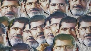 Des partisans de l'ancien président Morsi brandissent des masques lors d'un rassemblement au Caire, le 1er août.