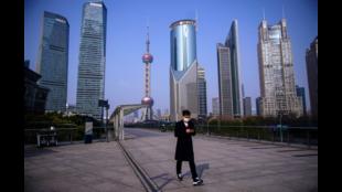 图为一名男子带着口罩,走在上海陆家嘴金融区的天桥上 2020年2月 资料照片