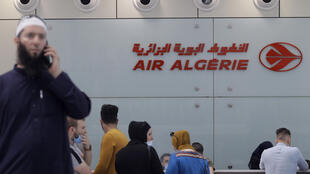 Passengers wait to check in at an Air Algeria counter for a flight to Paris at Algiers' Houari Boumediene Airport