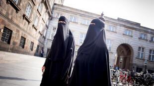 Mulheres são fotografadas usando o niqab em frente ao Parlamento da Dinamarca, em 31 de maio de 2018.