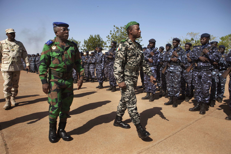Côte d'Ivoire army chief-of-staff Soumaila Bakayoko (L) and Malian army chief-of-staff Ibrahima Dahirou Dembele (C) inspect Malian troops at an air base in Bamako, Mali