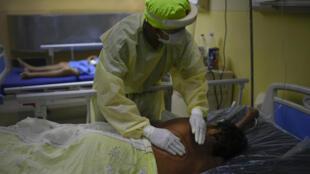 Un soignant d'un hôpital de Caracas s'occupe d'un patient atteint du Covid-19, le 28 mars 2021.