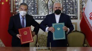 Los ministros Wang Yi (izq) y Mohammad Javad Zarif, chocando el codo, posan con sendas copias del acuerdo de cooperación chino-iraní, el 27 de marzo de 2021 en Teherán