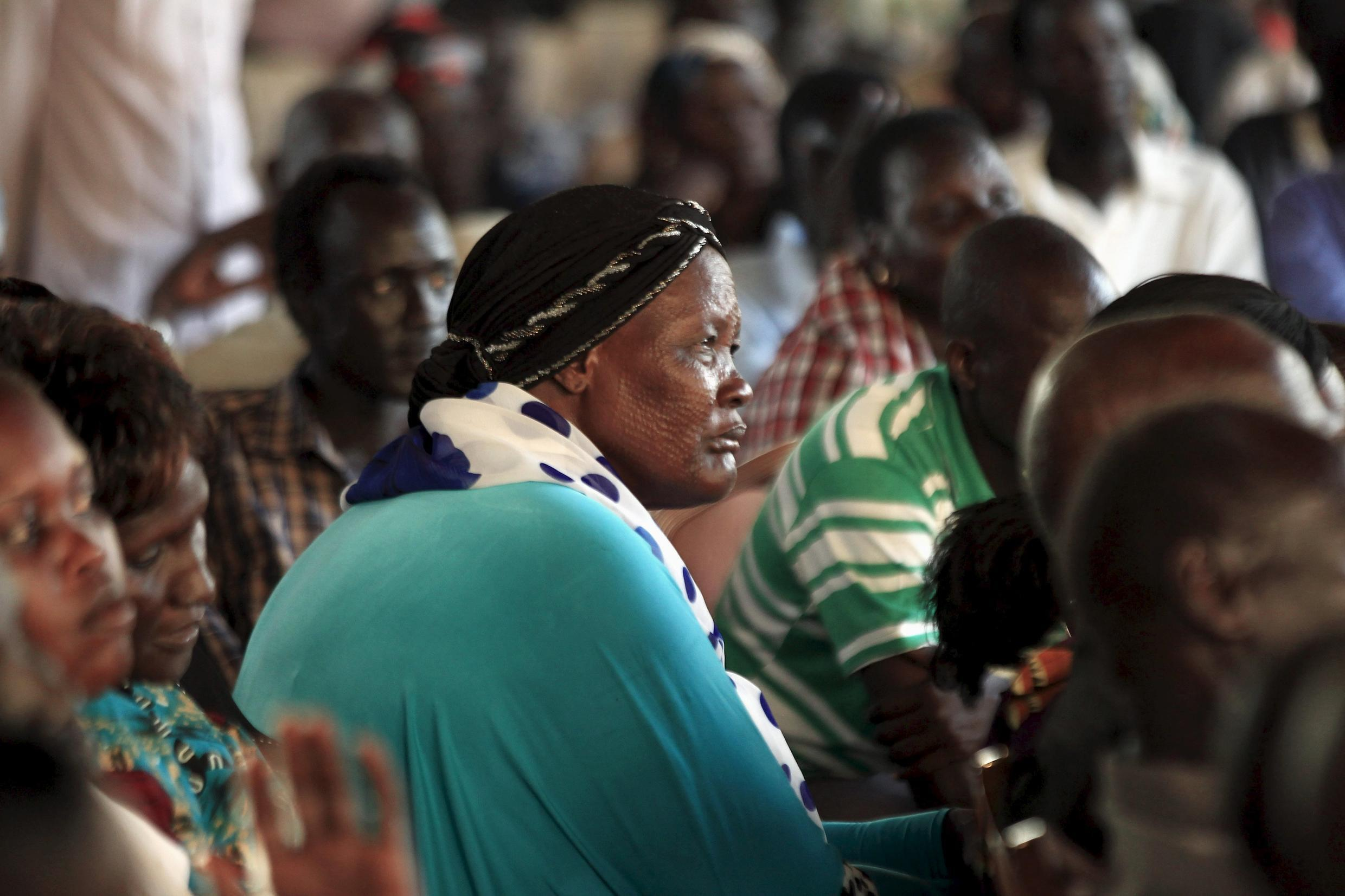 South Sudanese people living in the north of Sudan listen as South Sudan rebel leader Riek Machar talks during a news conference in Khartoum,  September 18, 2015.