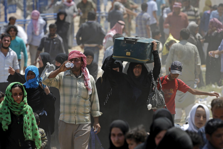 Quelque 10000 réfugiés syriens fuyant les combats marchent avec l'intention de traverser la frontière et  pénétrer coûte que coûte en Turquie à Akcakale (province de Saliurfa), en 2015.