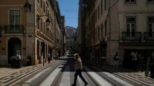 Mulher com máscara atravessa a rua em Lisboa