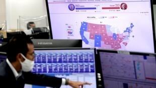 Un empleado de una compañía de cambio de divisas señala gráficos de cotizaciones de la Bolsa de Tokio ante una pantalla que muestra el escrutinio de las elecciones de EEUU, el 5 de noviembre de 2020 en la capital japonesa